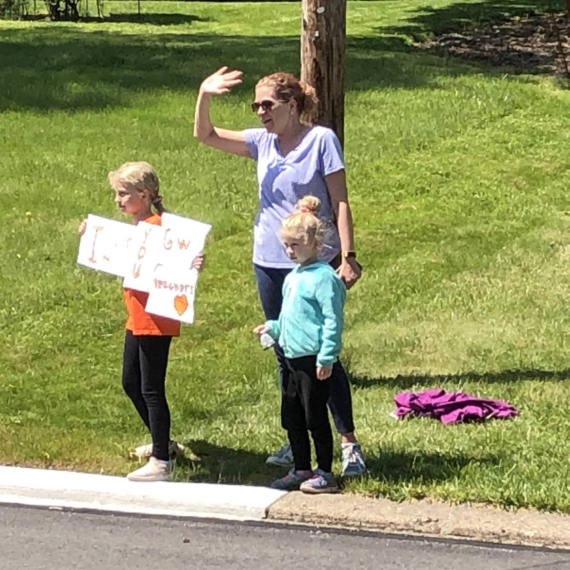 Two students and a parent waving