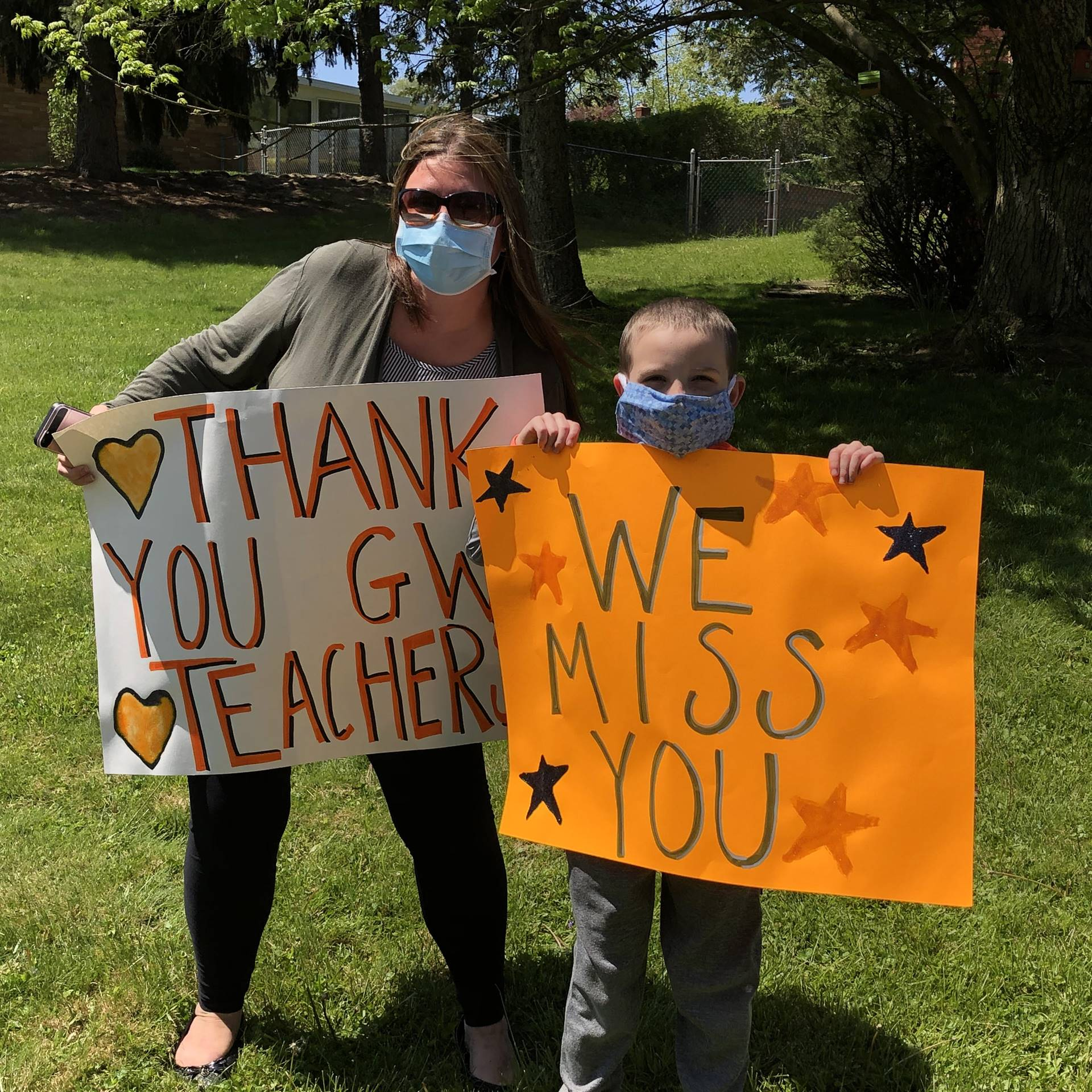 Student and parent holding signs