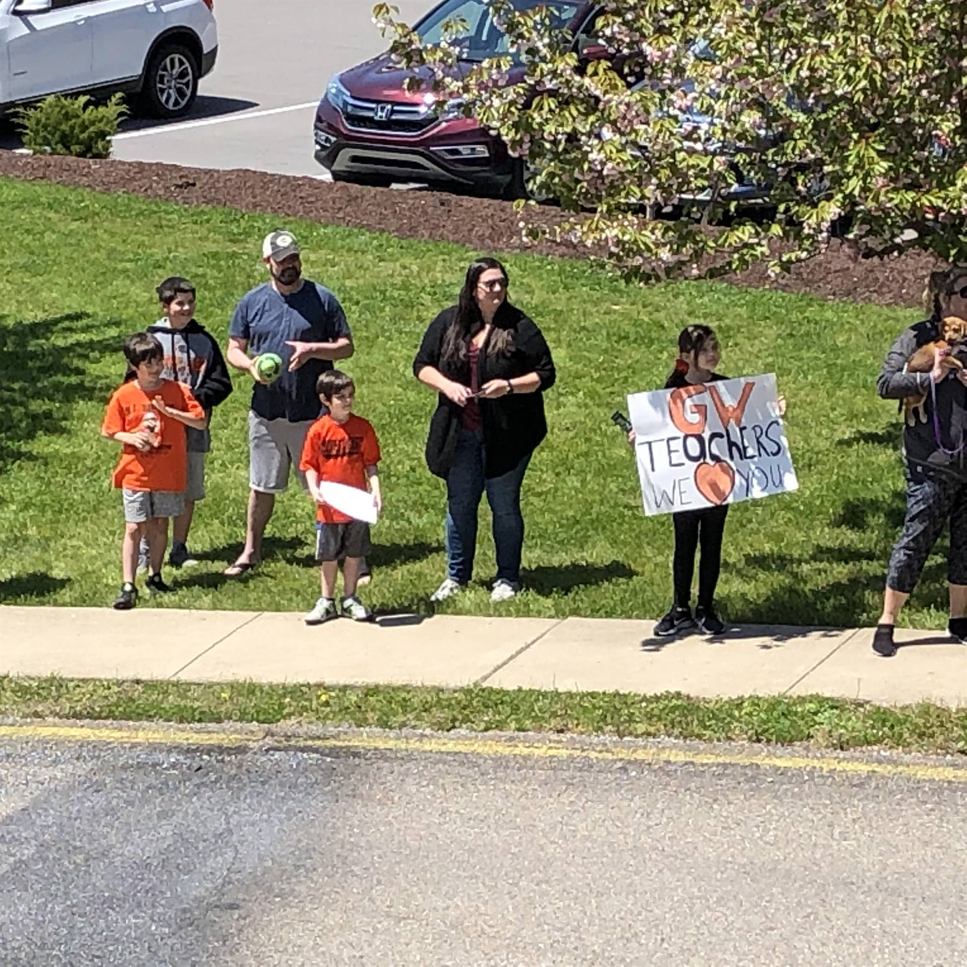 students and parents holding signs on the parade route