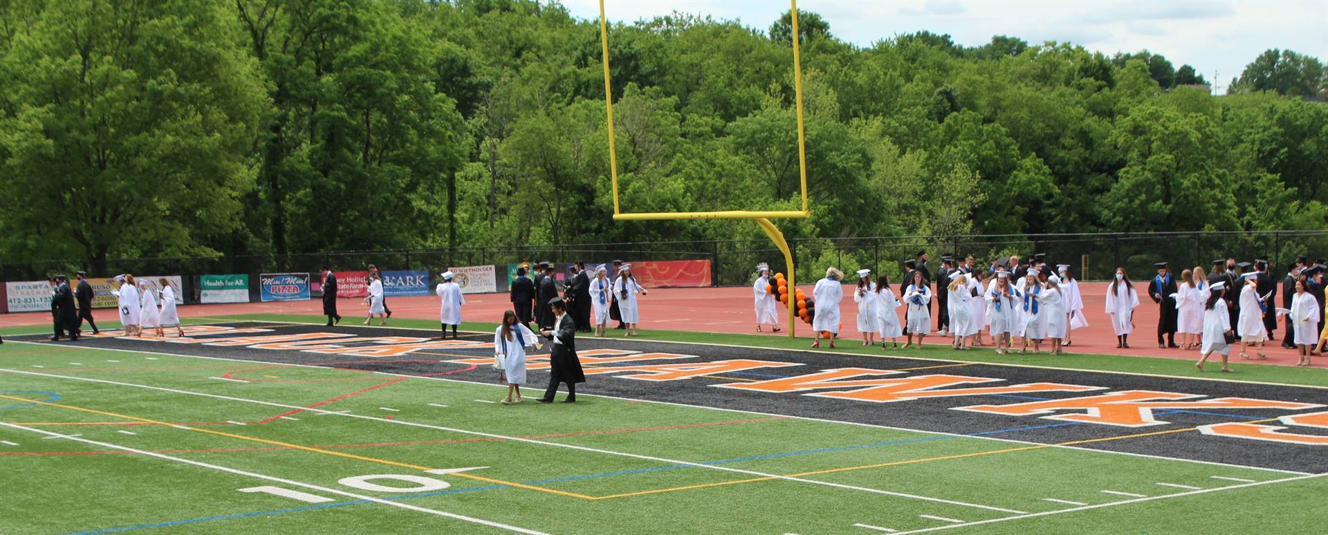 graduates gathering in the end zone