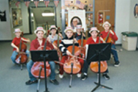 Elementary strings musicians wearing George Washington wigs